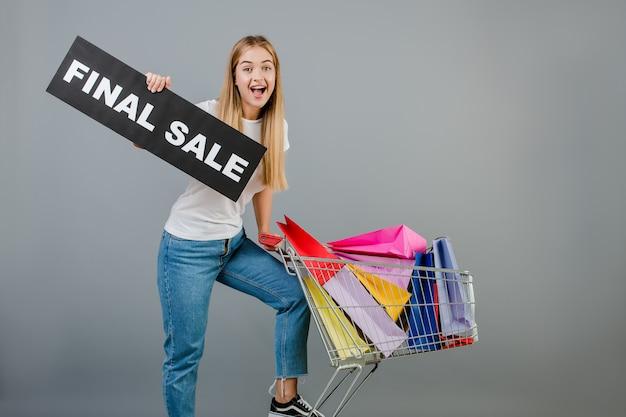 Menina animada com sinal de venda final e carrinho de mão cheio de sacolas coloridas isoladas sobre cinza