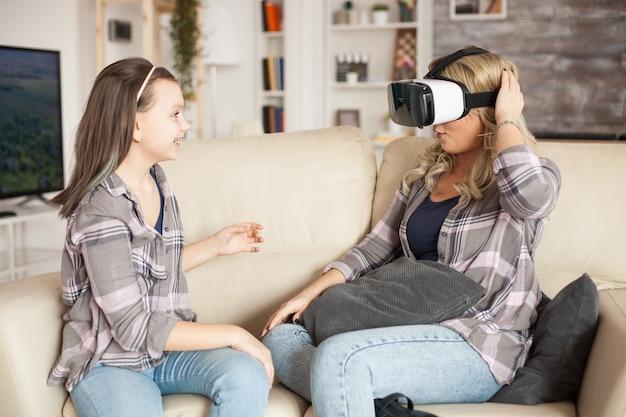 Menina animada com sua mãe usando fone de ouvido de realidade virtual.