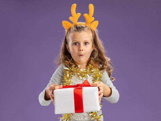 Menina animada com uma argola de cabelo de natal e uma guirlanda no pescoço segurando uma caixa de presente para a câmera isolada sobre fundo azul