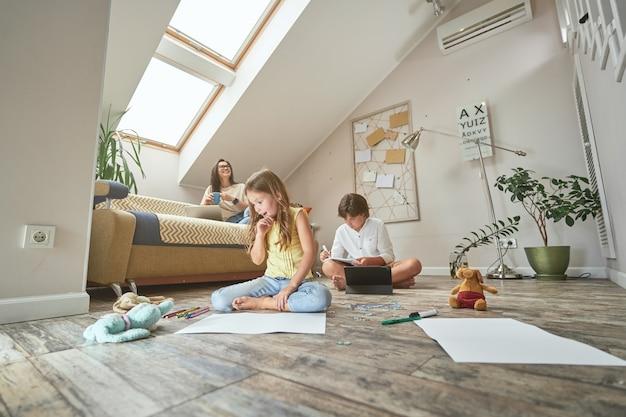 Menina animada e fofa sentada no chão desenhando com lápis coloridos enquanto o irmão dela faz