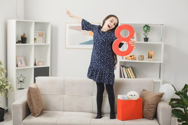 Menina animada espalhando a mão no feliz dia da mulher segurando o número oito, de pé no sofá da sala
