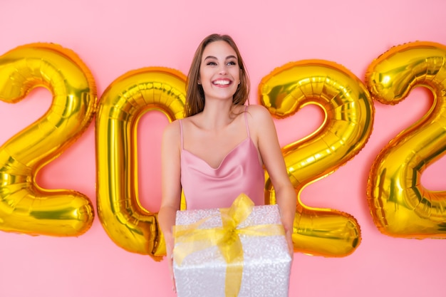 Menina animada segurando uma caixa de presente prata isolada em um fundo rosa, balões de ar, celebração de ano novo