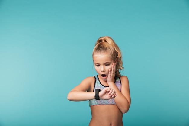 Menina animada vestindo roupas esportivas usando relógio inteligente isolado sobre a parede azul