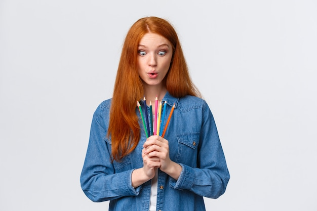 Menina ansiosa para iniciar um novo curso de arte, aprender a projetar, fazer modelos, em pé com lápis de cor