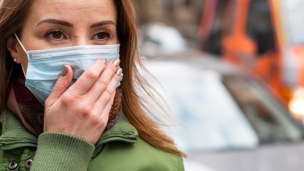 Menina ao ar livre, segurando sua máscara médica com a mão suja