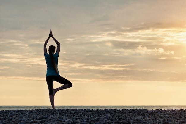 Menina ao pôr do sol praticando ioga à beira-mar, vista traseira