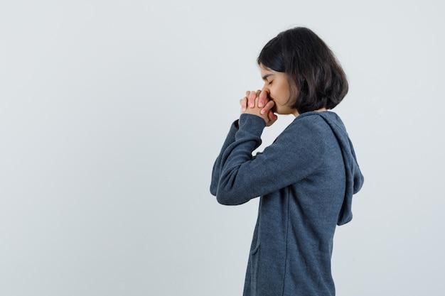 Menina apertando as mãos em gesto de oração na t-shirt, jaqueta e olhando esperançosa.