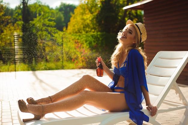 Menina, aplicar protetor solar nas pernas e deitado numa espreguiçadeira