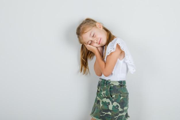 Menina apoiada nas palmas das mãos como travesseiro em camiseta branca, saia e parecendo com sono.