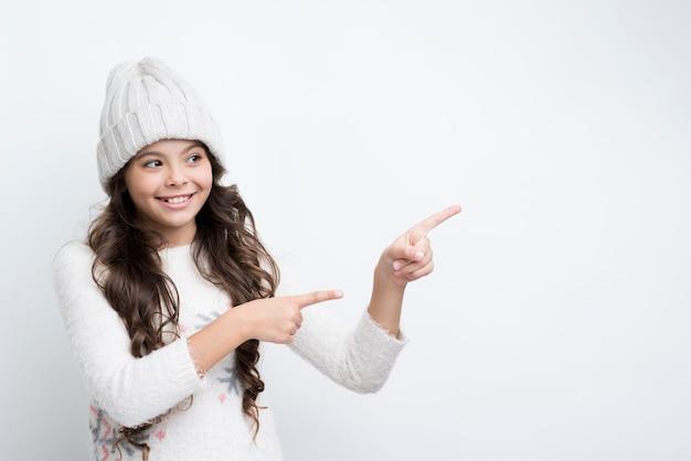 Menina apontando com os dedos para a esquerda