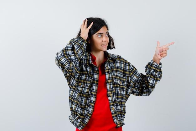 Menina apontando de lado em camisa, jaqueta e olhando focado. vista frontal.