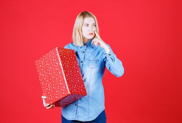 Menina apontando o rosto com o dedo e segurando seu presente no vermelho