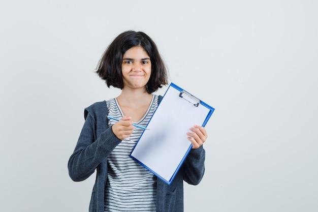 Menina apontando para a prancheta com lápis na camiseta, jaqueta e parecendo confiante,