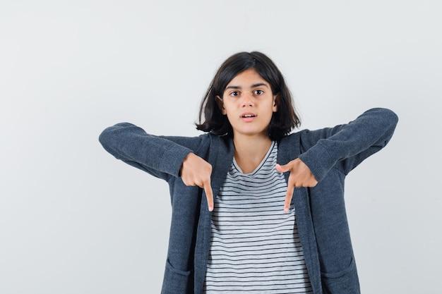 Menina apontando para baixo em camiseta, jaqueta e parecendo curiosa