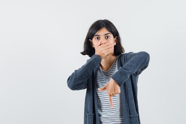 Menina apontando para baixo, segurando a mão na boca em uma camiseta, jaqueta e parecendo surpresa.