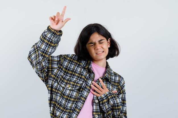 Menina apontando para cima na camisa, vista frontal da jaqueta.