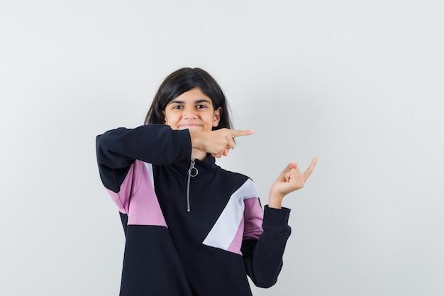 Menina apontando para o lado direito da camisa e olhando feliz. vista frontal.