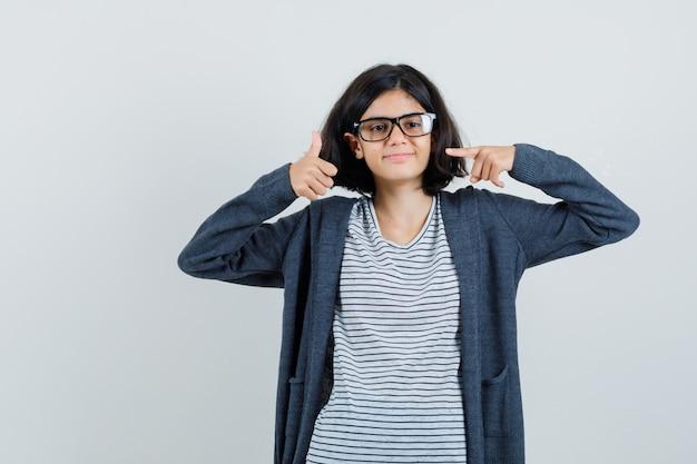 Menina apontando para o polegar para cima em t-shirt, jaqueta e parecendo feliz.