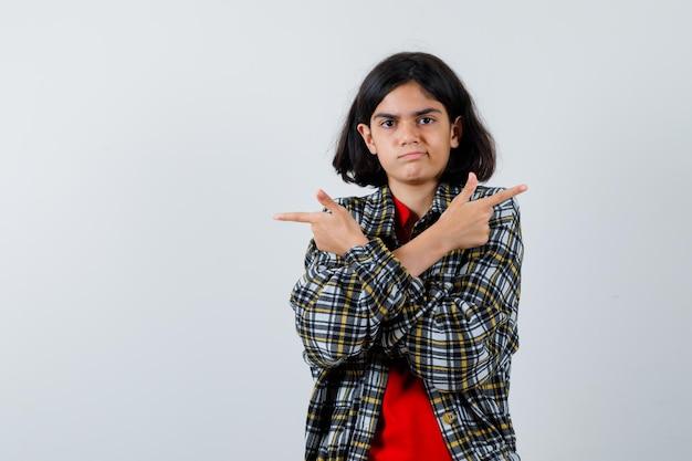 Menina apontando para o verso com as mãos cruzadas na camisa, jaqueta e parecendo confusa. vista frontal.