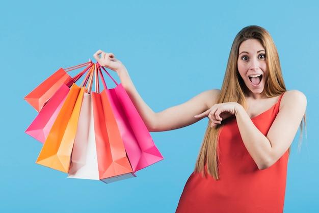 Menina apontando para sacolas de compras