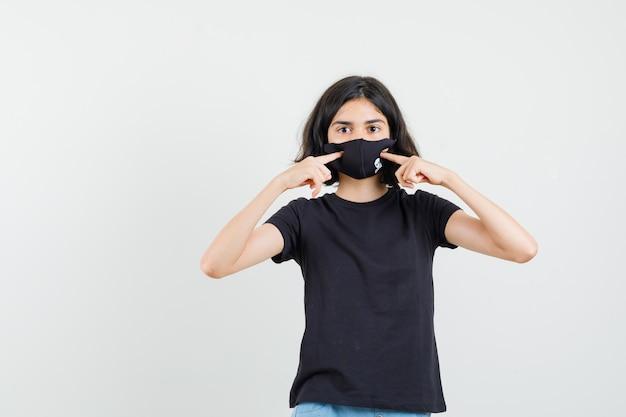 Menina apontando para sua máscara em vista frontal de t-shirt, shorts preto.