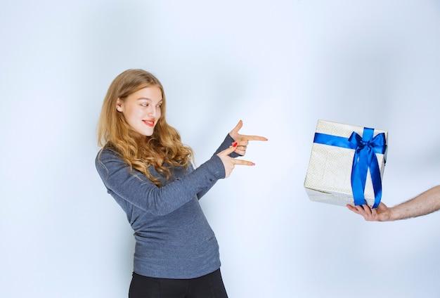 Menina apontando uma caixa de presente azul branca oferecida a ela.