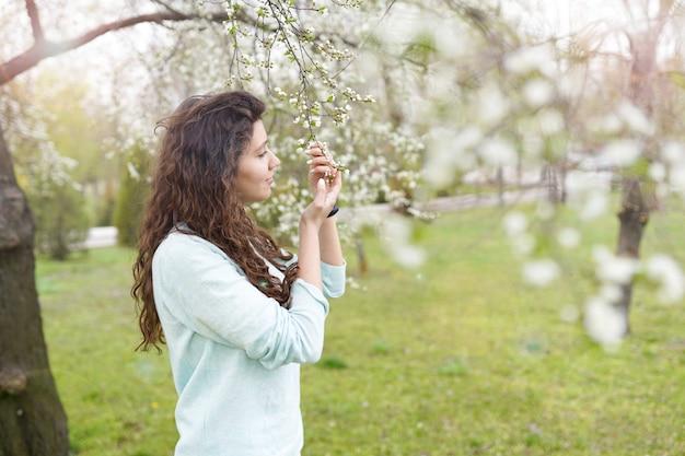 Menina, apreciando o cheiro em um jardim florido