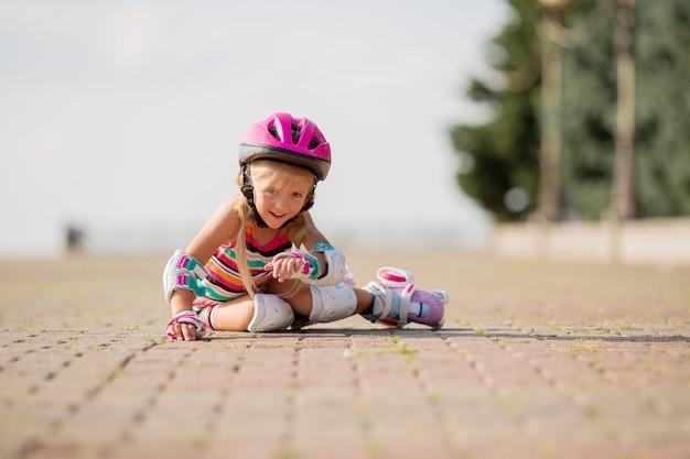 Menina aprende a andar de patins no verão