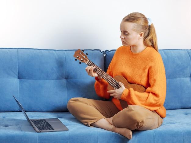 Menina aprende a tocar ukulele remotamente
