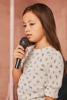 Menina aprendendo a cantar em casa com o microfone