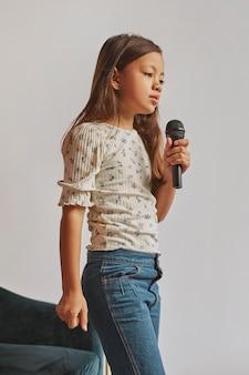 Menina aprendendo a cantar em casa