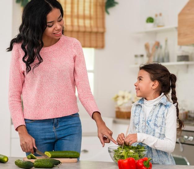 Menina aprendendo a cozinhar com a mãe
