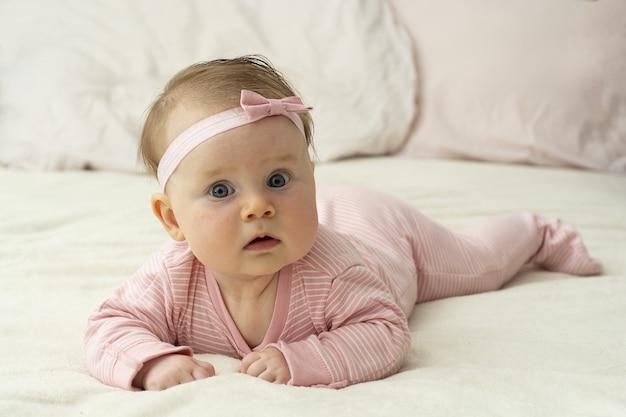 Menina aprendendo a deitar de barriga, novas habilidades.