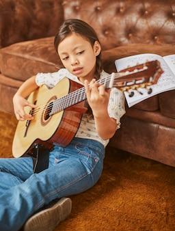 Menina aprendendo a tocar violão em casa