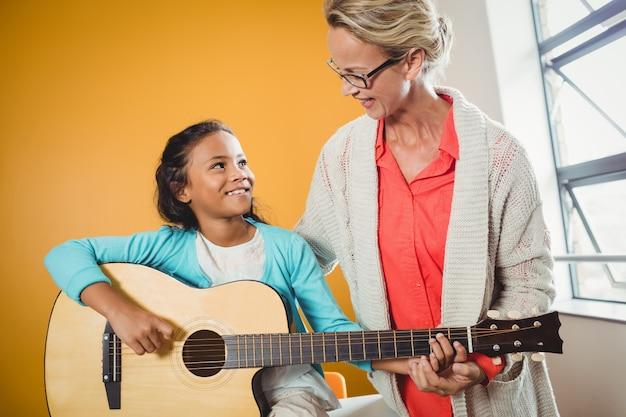 Menina aprendendo a tocar violão