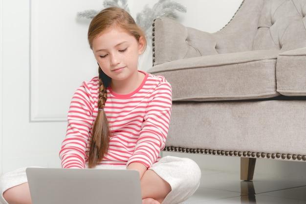 Menina aprendendo com o computador em casa.