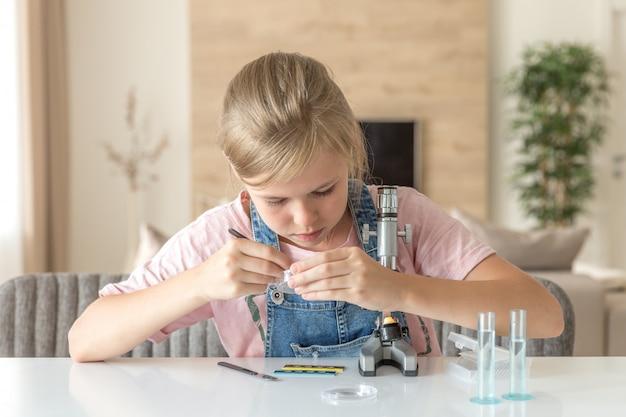 Menina aprendendo química brincando com o microscópio em casa
