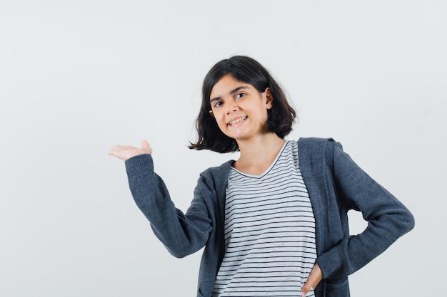 Menina apresentando algo ou dando boas-vindas em t-shirt, casaco e parece confiante.