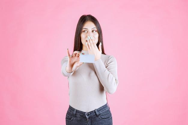 Menina apresentando seu cartão de visita e pedindo silêncio