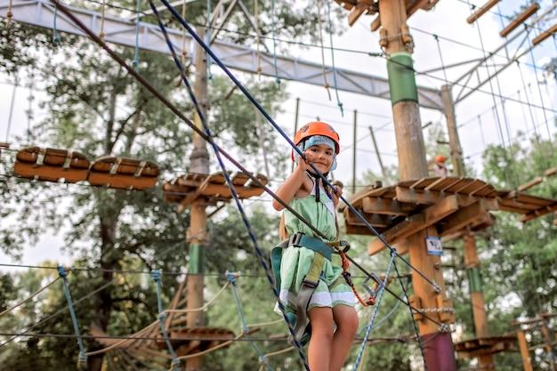 Menina, aproveitando o tempo em uma estrutura de corda no parque de aventura