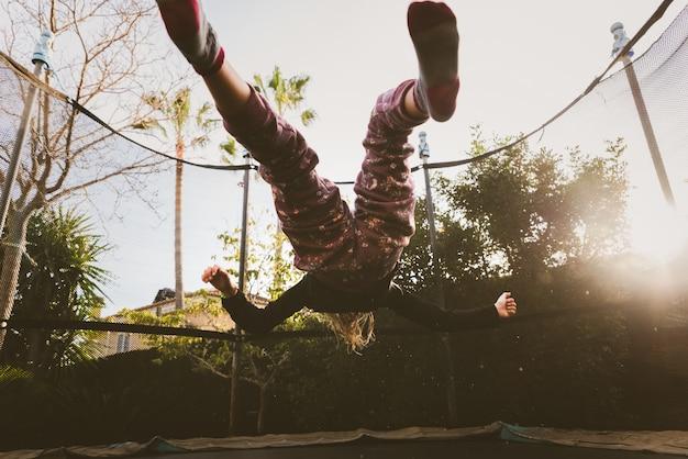 Menina, aproveitando suas férias pulando no trampolim, fazendo exercícios acrobáticos ao ar livre.