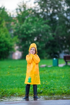 Menina aproveite a chuva em um dia quente de outono
