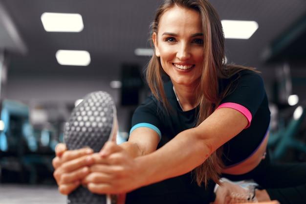 Menina apta a fazer exercícios de alongamento para as pernas