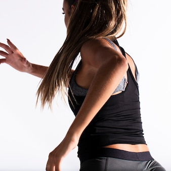Menina apta no terno de ginástica correndo dentro de casa