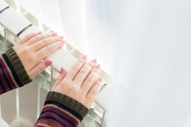 Menina aquece as mãos congeladas acima do radiador quente, close-up vista