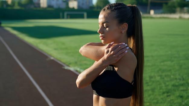 Menina aquecendo a parte superior do corpo no estádio pela manhã