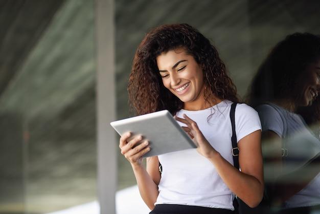 Menina árabe de sorriso que usa a tabuleta digital no fundo do negócio.