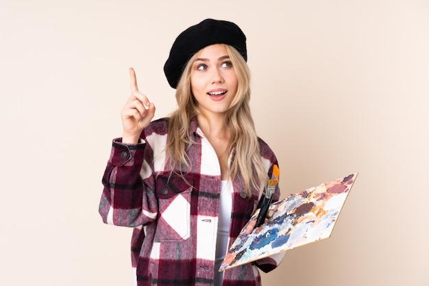 Menina artista adolescente segurando uma paleta isolada em azul