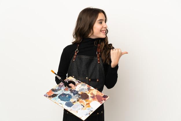 Menina artista segurando uma paleta isolada na parede branca apontando para o lado para apresentar um produto