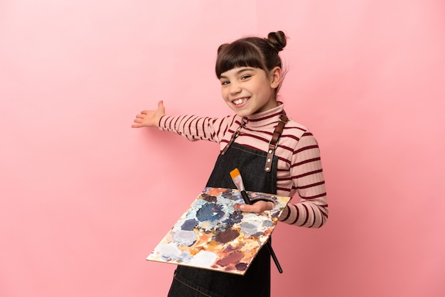 Menina artista segurando uma paleta isolada na parede rosa, estendendo as mãos para o lado para convidar para vir
